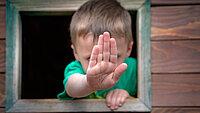 Kleiner Junge der durch ein Fenster schaut und Stopp-Handzeichen zeigt