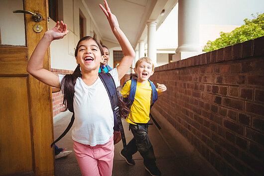 Lachende Schulkinder rennen aus dem Klassenraum