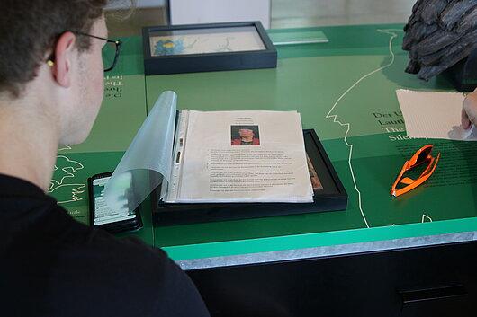 Schüler beim Lesen eines Factsheets